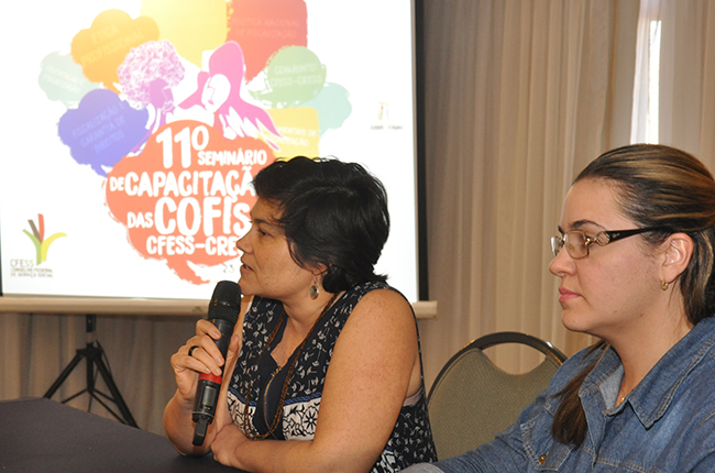 Imagem mostra a vice-presidente do CFESS Daniela Neves na mesa de encerramento