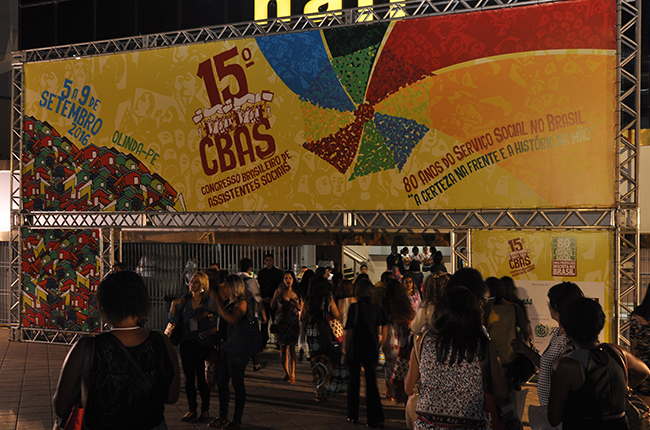 Imagem mostra painel montado com arte do CBAS, que traz elementos da cultura Pernambucana, como  uma ilustração de uma sombrinha do frevo, alguns desenhos rústicos como cordéis, casas coloridas etc.