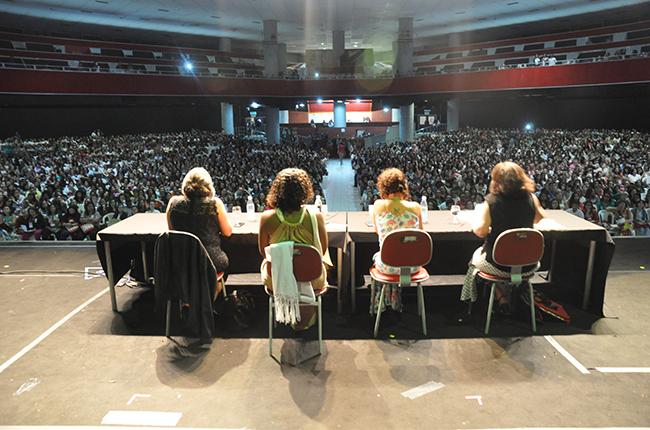 Imagem mostra vista panorâmica do palco onde estava as palestrantes da conferência de abertura e o público ocupando grande parte do local