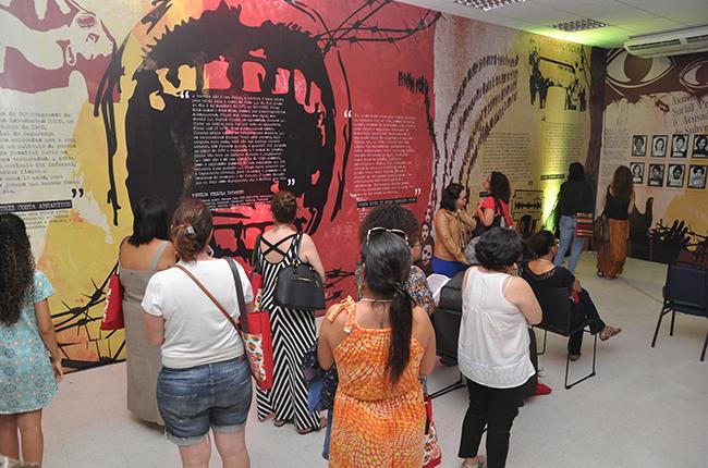Imagem mostra participantes na exposição sobre o serviço social e a ditadura militar. Os painéis trazem imagens que remetem à ditadura e textos de assistentes sociais que lutaram pela democracia