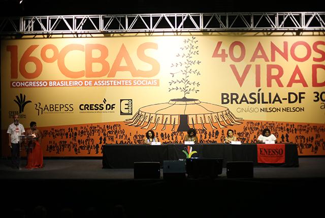 Foto do palco no ginásio Nilson Nelson. Uma mesa com representantes das entidades organizadoras, o cerimonial à esquerda e ao fundo uma grande tela com a arte do evento, uma ilustração que reproduz o ginásio com a árvore do Código de Ética no topo