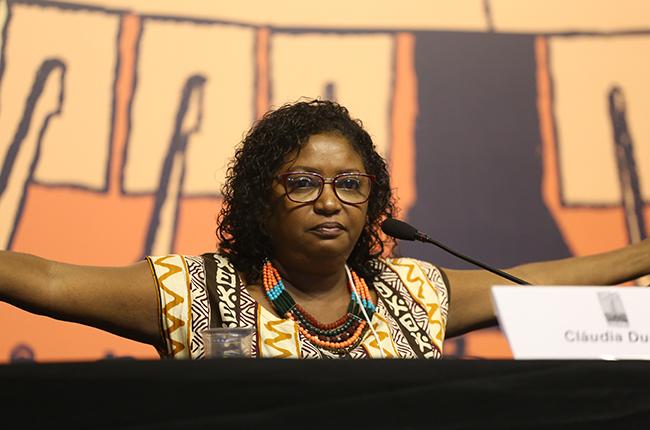 Foto de Cláudia Durans, mulher negra que está de braços em frente ao público para reafirmar a resistência do povo negro