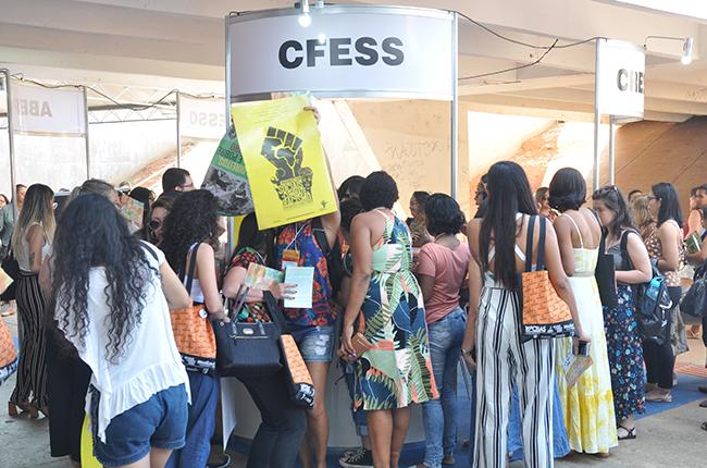 Foto mostra várias congressistas em volta do estande do CFESS buscando os materiais