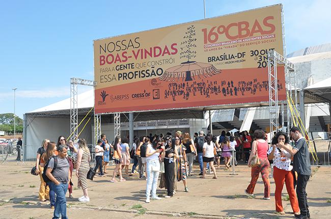 Foto da entrada do Ginásio, com a uma placa grande de boas vindas às congressistas, que caminham em direção ao Ginásio