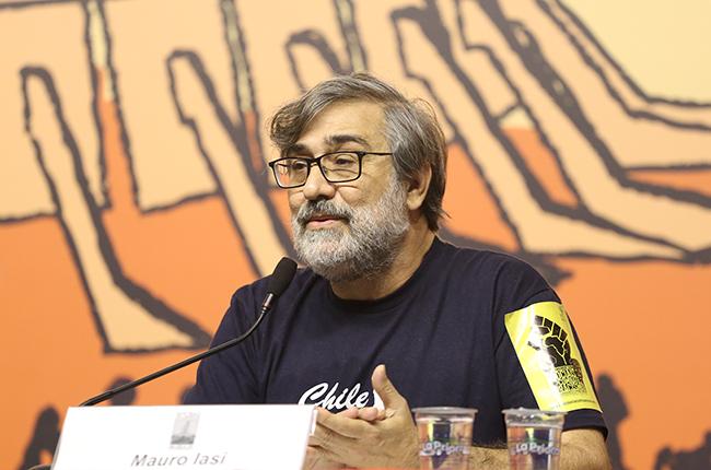 Foto do palestrante Maurio Iasi, de barba grisalha e óculos, falando para o público