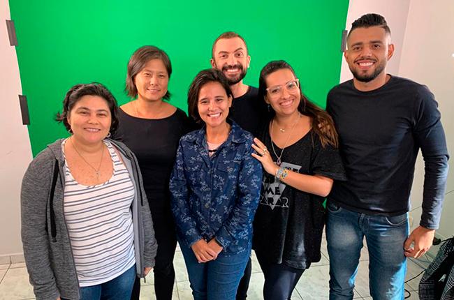 Imagem mostra equipe de tradutores/as e intérpretes de libras, juntamente com a equipe do CFESS, no local onde foi gravado o vídeo.