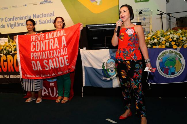 Imagem mostra a conselheira do CFESS Elaine Pelaez durante tribuna na Conferência. Ao fundo, duas mulheres seguram a faixa da Frente Nacional Contra a Privatização da Saúde