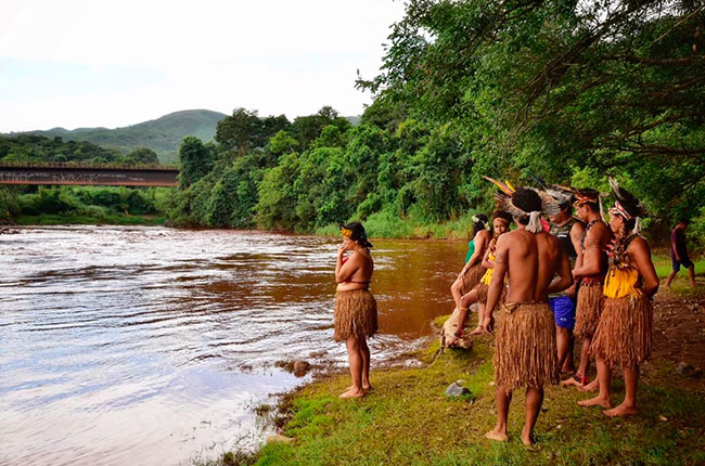 Imagens de indígenas em frente ao Rio Paraopeba, poluído com a lama tóxica de rejeitos.