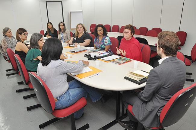 Imagem do grupo que foi até o MEC, sentado ao redor da mesa de reuniões, no momento em que a conselheira do CFESS Daniela Castilho fala.