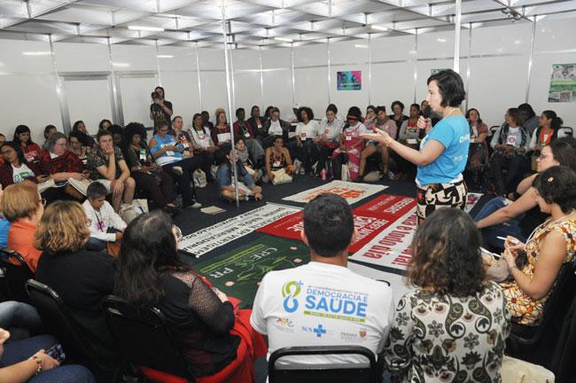 Imagem da reunião com assistentes sociais, reunidas em círculo, com a conselheira do CFESS Elaine Pelaez em pé falando.