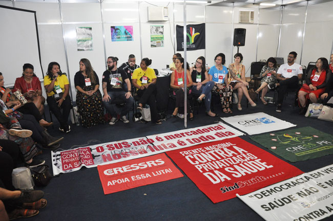 Imagem de Assistentes sociais reunidos em círculo se apresentando durante o debate com a diretoria do CFESS.