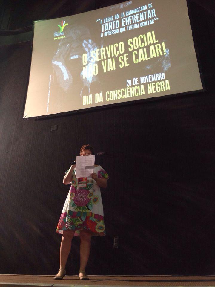 Imagem da conselheira do CFESS Daniela Castilho declamando um poema sobre a consciência negra, durante o evento