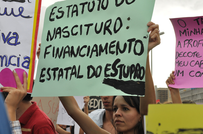 Foto de jovem segurando cartaz com os dizeres: Estatuto do Nascituro - financiamento estatal do estupro