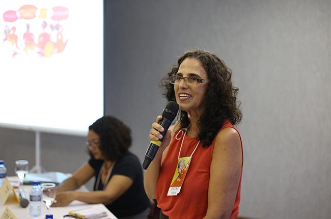 Imagem mostra a conselheira do CFESS Neimy durante sua fala no auditório