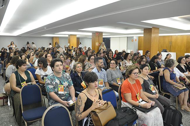 Imagem do auditório com cerca de 60 pessoas assistindo à mesa de debate