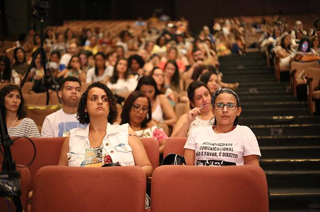 Fotografia de parte da plateia. Em destaque, uma assistente social vestindo uma camiseta em defesa da acessibilidade