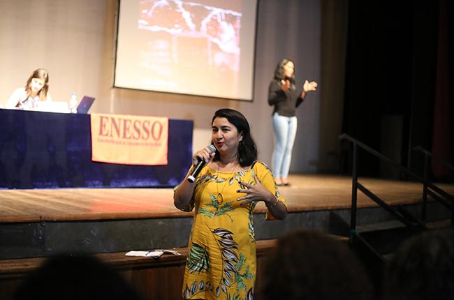 Imagem mostra participante em pé, segurando microfone para fazer uma pergunta aos palestrantes.