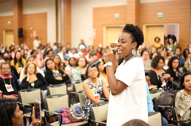 Imagem mostra artista negra fazendo sua apresentação diante do público do evento