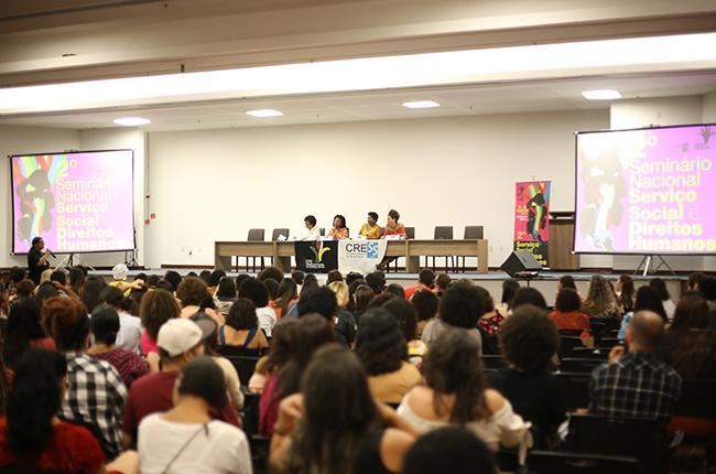 Fotografia feita na parte de trás do auditório mostra as pessoas assistindo à mesa de debates