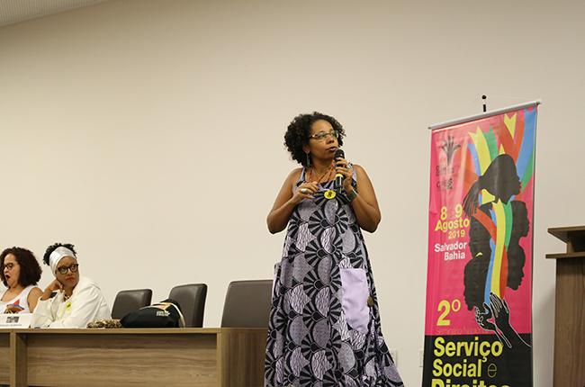Fotografia da presidente do CFESS Josiane Soares em pé apresentando slides