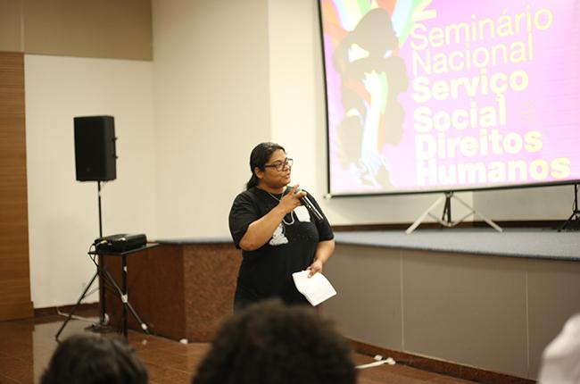 Imagem mostra participante fazendo uma pergunta para as palestrantes