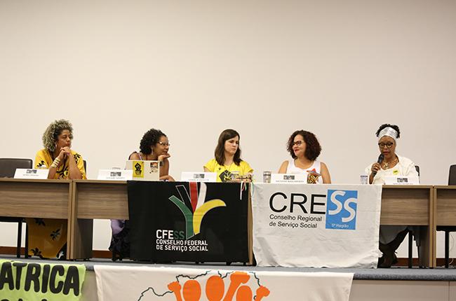 Fotografia da mesa de debates na qual todas palestrantes e moderadoras aparecem