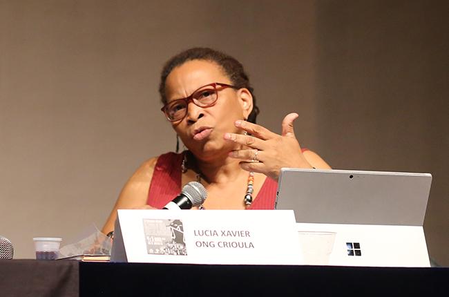 Imagem mostra fotografia de Lúcia Xavier na mesa-redonda falando para o público