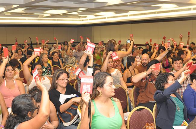 Imagem mostra participantes no auditório levantando o crachá de votação