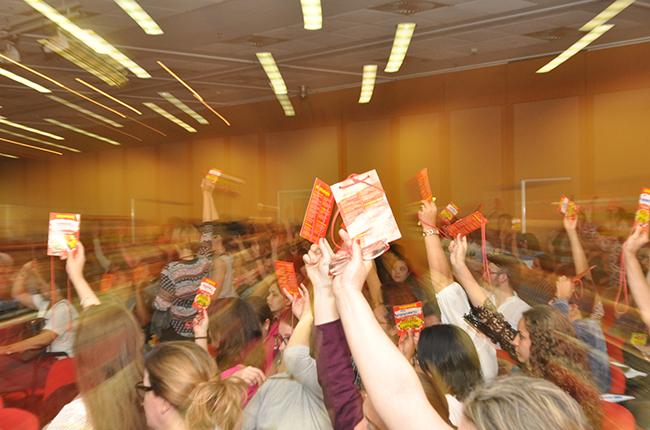 Imagem de participantes do evento com crachás levantados, no momento da votação
