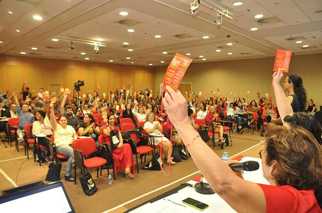Imagem mostra plenária com participantes levantando seus crachás