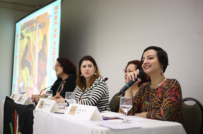 Foto mostra a conselheira do CFESS Elaine Pelaez na mesa de encerramento do evento. Elaine está sorrindo para a Plenária