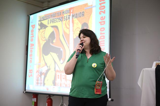 Imagem mostra a conselheira de São Paulo no momento em que ela avalia o evento. Ela está em pé, em frente ao palco, segurando o microfone
