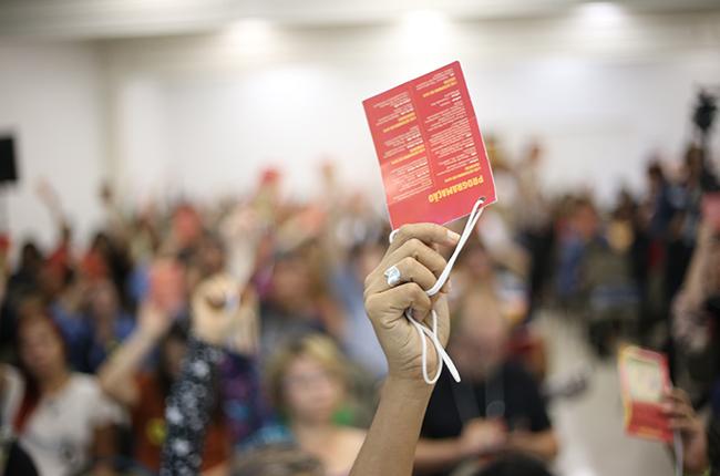 Imagem mostra mão de mulher em destaque, segurando o crachá vermelho de delegada no momento da votação. Ao fundo da imagem está o restante da plenária, desfocado.