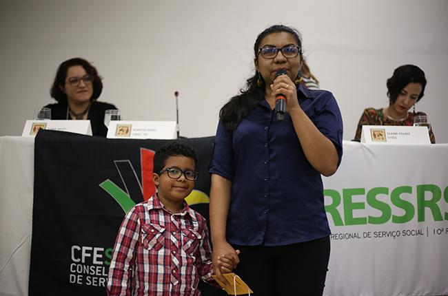 Imagem mostra a assistente social Elda e seu filho Pedro. Elada segura o microfone para fazer a avaliação do evento. Seu filho está de mãos dadas com ela, sorrido para a foto. Ele ficou no espaço reservado para as crianças, para que as mães e pais possam participar do evento