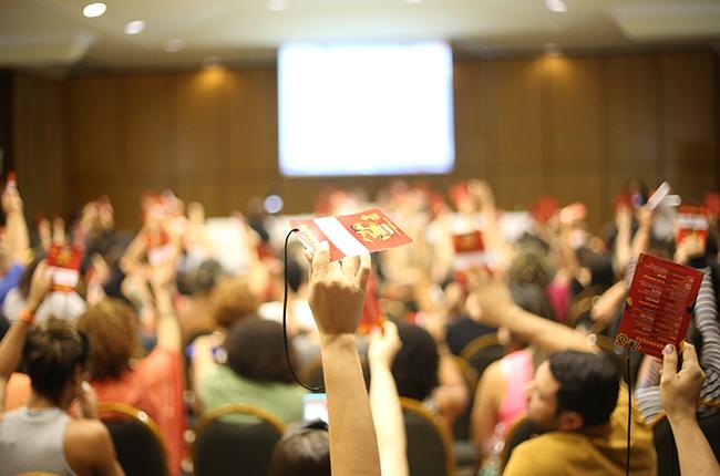 Fotografia mostra participantes durante a plenária final, erguendo o crachá vermelho para aprovar as deliberações do Encontro