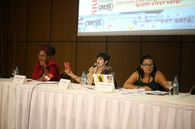 Foto mostra as integrantes da mesa que conduziram a Plenária Final. Nela, as integrantes estão segurando o microfone para dar orientações aos/às participantes