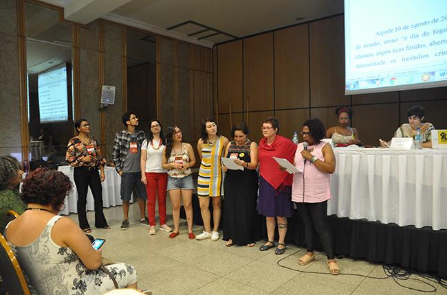 Imagem mostra o momento da leitura da carta de Belém. Na imagem, as assistentes sociais que elaboraram a carta estão em pé, em frente à mesa de debates, fazendo a leitura do texto.