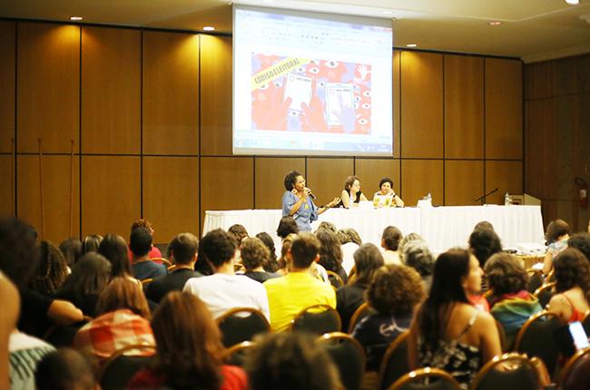 Fotografia do auditório onde ocorreu a Plenária. Josiane está em pé, apresentando as informações sobre como vai funcionar a eleição virtual