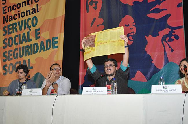 Imagem do presidente do CFESS, lançando o folder com as bandeiras de luta do Serviço Social