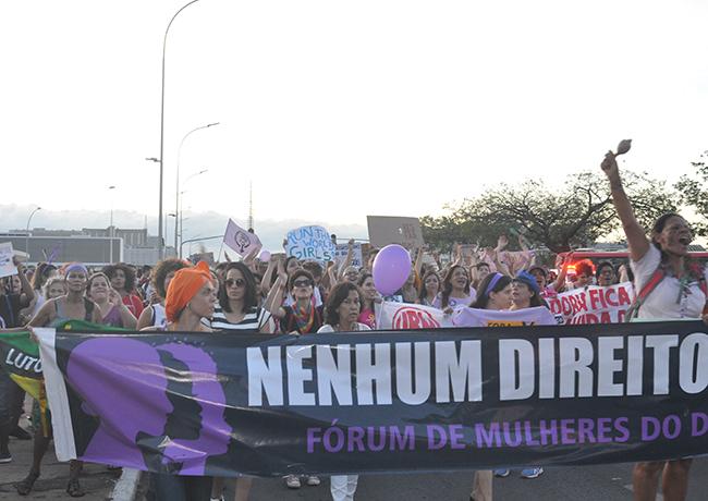 Imagem mostra mulheres levantando bandeiras com dizeres de luta caminhando em direção ao Congresso Nacional