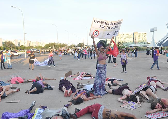 Foto mostra mulheres num ato teatral representando o feminicídio