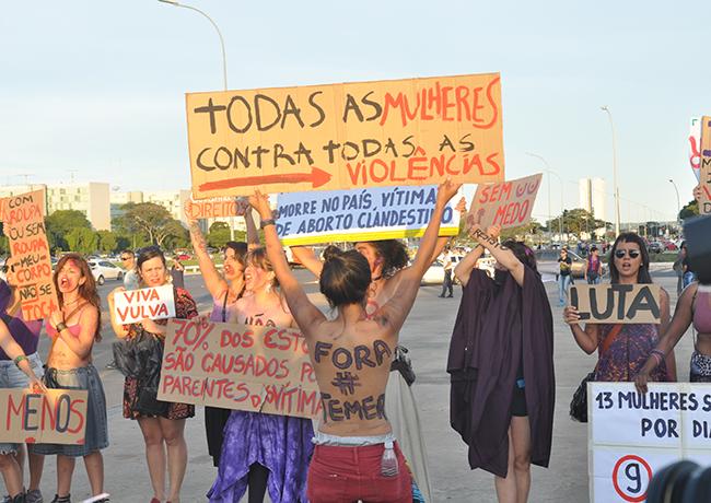 Imagem mostra mulheres segurando faixas denunciando a violência de gênero