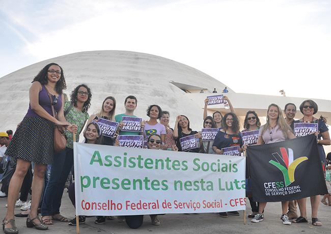 Foto mostra assistentes sociais juntas próximas à faixa do CFESS e com o Museu Nacional ao fundo