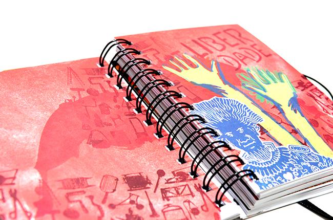 Imagem mostra ilustração interna da agenda, fazendo referência à pessoa de Arthur Bispo do Rosário, em traços rústicos e cores vivas, como rosa, amarelo, azul etc.