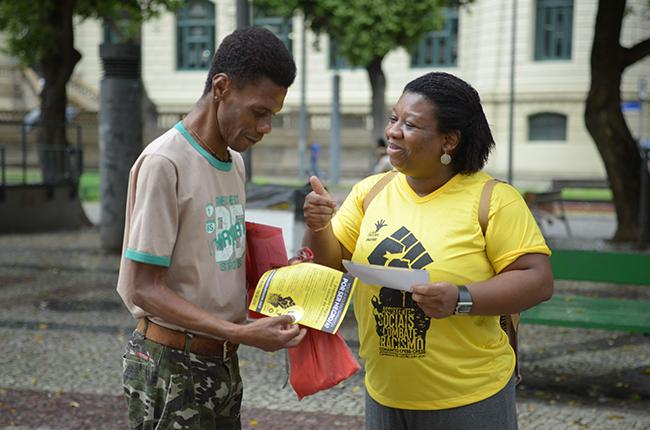 Imagem mostra a assistente social e conselheira do CFESS, Solange Moreira, vetsida com uma camisa amarela com a logomarca da campanha em preto, abordando um senhor negro na rua para falar da campanha. O homem manifesta interesse e recebe o material