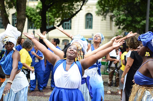 Imagem mostra dança do grupo Filhas de Ghandy. As mulheres negras estão de roupa azul e branco, olhando para o céu, de braços abertos.