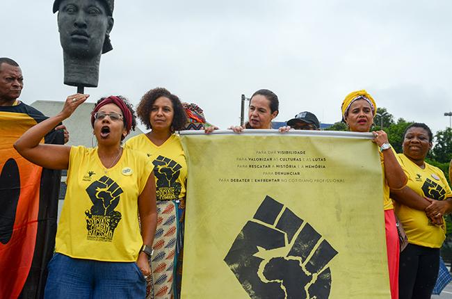 Imagem mostra a presidente do CFESS Josiane Soares, ao lado da presidente do CRESS-RJ, Dácia Teles, em fala em frente ao busto em homenagem a Zumbi
