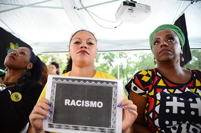 Imagem mostra mulheres negras assistindo à aula pública sobre racismo, na tenda montada pelo CFESS e CRESS-RJ. Uma delas segura o cartaz escrito a palavra racismo