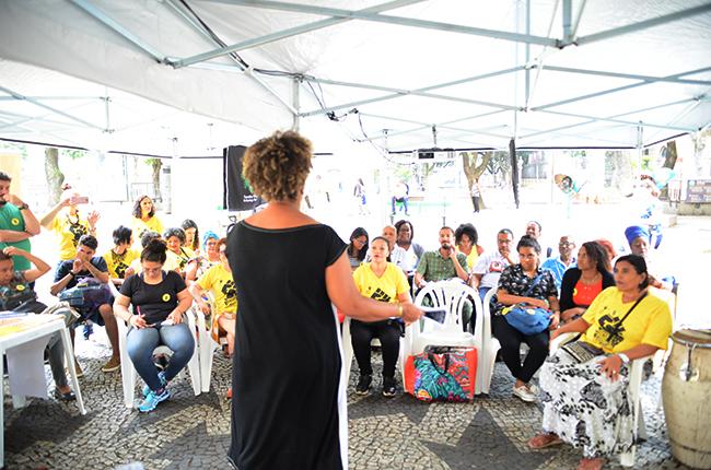 Imagem mostra várias pessoas sentadas, sob a tenda montada para a atividade, assistindo à aula da assistente social Roseli Rocha sobre racismo.