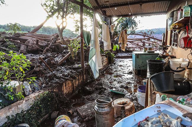 Imagem de árvores destruídas e uma casa abandonada após passagem da lama da barragem de Brumadinho.